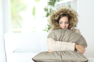Woman warmly clothed in a cold home - Heating Service Gilbert AZ